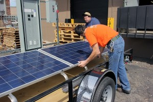 carefully placing panels on horace mobile solar energy demo unit