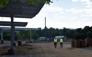 Brightergy project managers walk the solar canopy installation site at UMass Amherst
