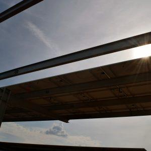 sun shining through solar panels at UMass Amherst
