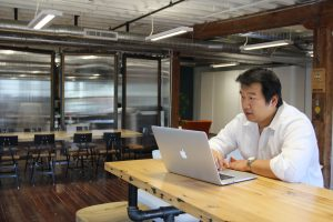 Bruce Wang at his laptop in Brightergy office